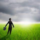Rilassi la borsa della tenuta della donna di affari nel giacimento e nei rainclouds verdi del riso Fotografia Stock Libera da Diritti