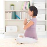 Rilassi la donna incinta che medita a casa Immagini Stock