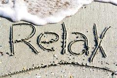 Rilassi la parola scritta a mano sulla sabbia, sulla spiaggia Immagine Stock Libera da Diritti