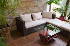 Rilassi la zona in conservatorio con la tavola dal sofà del rattan e del motore fotografie stock