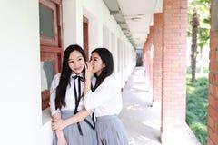 Rilassi lo studente che grazioso cinese asiatico di usura delle ragazze il vestito a scuola gode del gossip di tempo libero in au Fotografie Stock