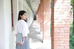 Rilassi lo studente che grazioso cinese asiatico di usura delle ragazze il vestito a scuola gode del libro colto tempo libero nel Fotografie Stock