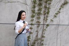 Rilassi lo studente che grazioso cinese asiatico di usura delle ragazze il vestito a scuola gode dell'acqua della bevanda di temp Fotografia Stock Libera da Diritti