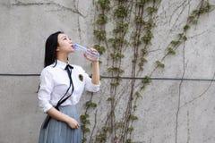 Rilassi lo studente che grazioso cinese asiatico di usura delle ragazze il vestito a scuola gode dell'acqua della bevanda di temp Fotografia Stock