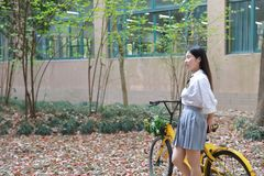 Rilassi lo studente che grazioso cinese asiatico di usura delle ragazze il vestito a scuola gode della bici di giro di tempo libe Immagini Stock