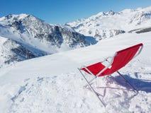 Rilassi in questa sedia nella neve su una cima della montagna immagini stock libere da diritti