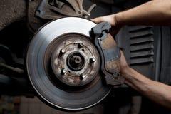 Rilievi di freno di riparazione del meccanico di automobile Fotografie Stock