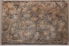 Rilievo assyrian antico che descrive i dei alati o s Immagini Stock