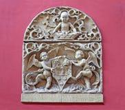 Rilievo di pietra dell'emblema dalla facciata antica della casa fotografia stock