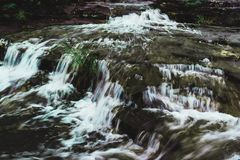 Rill. A small stream of water turning to a fierce waterfall ahead Stock Images