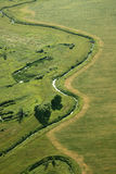 Rill. Stream flowing among green fields Stock Photos