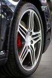 Rim. Alloy rim with tyre mounted on black car Stock Images