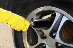 Rim brush. Woman's hand with a rim brush cleaning a wheel of an SUV car Royalty Free Stock Image