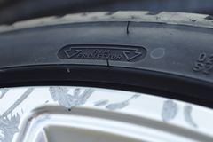 Rim protection feature at the sidewall of a high perfomance car tire mounted on a scraped aluminum rim. Close up view on the rim protection feature at the ewall stock photo