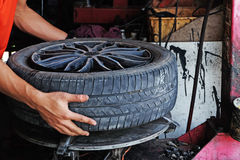 Rim with tyre is handled and repaired by technician Stock Photo