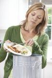 Rimanenze di raschio dell'alimento della donna nel bidone della spazzatura Immagine Stock