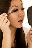 Rimel de aplicación adolescente americano asiático que sostiene el espejo de mano Foto de archivo
