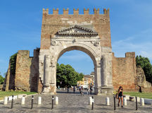Rimini - Augustus Arch. Rimini, Italy - June 21, 2017: Unidentified people walk under Augustus Arch - the ancient romanesque gate and the historical landmark of Stock Photography