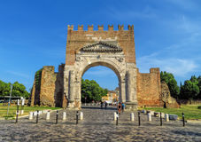 Rimini - Augustus Arch. Rimini, Italy - June 21, 2017: Unidentified people walk under Augustus Arch - the ancient romanesque gate and the historical landmark of Stock Photos
