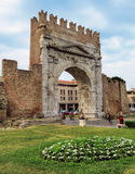 Rimini - Augustus Arch. Rimini, Italy - June 14, 2017: Unidentified people walk under Augustus Arch - the ancient romanesque gate and the historical landmark of Royalty Free Stock Photography