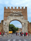 Rimini- Augustus Arch. Rimini, Italy - June 14, 2017: Unidentified people walk under Augustus Arch - the ancient romanesque gate and the historical landmark of Stock Photos