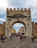 Rimini- Augustus Arch. Rimini, Italy - June 14, 2017: Unidentified people walk under Augustus Arch - the ancient romanesque gate and the historical landmark of Stock Images