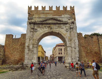 Rimini - Augustus Arch. Rimini, Italy - June 14, 2017: Unidentified people walk under Augustus Arch - the ancient romanesque gate and the historical landmark of Royalty Free Stock Photos