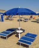 Rimini - Blue open umbrella and sunbeds Stock Photos