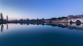 Rimini city landscape on riverside. Tiberius bridge and city park at sunset. Twilight view