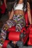 Rimini, Itália - em junho de 2017: Menina que faz exercícios no Gym: Exercício das extensões do pé na máquina da aptidão Foto de Stock