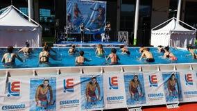 Rimini, Itália - em junho de 2019: Povos que fazem a ginástica aeróbica de água exterior em uma piscina com bicicleta, música e o vídeos de arquivo