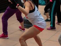 Rimini, Itália - podem 2016: Moça com short e camiseta de alças branca: Exercício do encaixotamento da aptidão com saco de perfur Foto de Stock