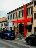 Rimini, Italy - December 26, 2014: Giant red ribbon at urban building. House decorated with Christmas ribbon. Rimini, Italy - December 26, 2014: Giant red ribbon royalty free stock images