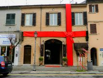 Rimini, Italy - December 26, 2014: Giant red ribbon at urban building. House decorated with Christmas ribbon. Rimini, Italy - December 26, 2014: Giant red ribbon royalty free stock image