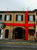 Rimini, Italy - December 26, 2014: Giant red ribbon at urban building. House decorated with Christmas ribbon. Rimini, Italy - December 26, 2014: Giant red ribbon royalty free stock photo