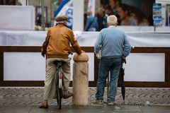 Rimini, Italy - june 2017: Rear View of Two Old Men in City Street: One on His Bicycle and the Other Standing with His Umbrella Royalty Free Stock Photo