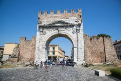 Rimini, Italy - June 21, 2017: Unidentified people walk under Au. Gustus Arch - the ancient romanesque gate and the historical landmark of Rimini, Italy Stock Photo