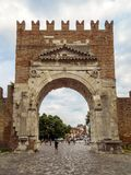 Rimini - Augustus Arch. Rimini, Italy - June 14, 2017: Unidentified people walk under Augustus Arch - the ancient romanesque gate and the historical landmark of Royalty Free Stock Photo