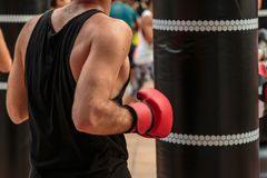 Rimini, Italy - may 2016: Fitness and Boxing Workout: Boy with Red Gloves and Black Punching Bag.  Stock Images