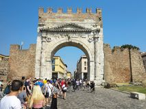 13.06.2017, Rimini, Italy - tourists near Arch of Augustus, anci. Ent romanesque gate of the city - historical italian landmark Royalty Free Stock Image
