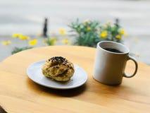Rimmad bakelse med Poppy Seeds Served med kaffe på kafét shoppar trädgårds- utvändig gatamat Arkivbilder