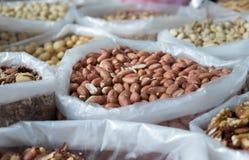 Rimmade grillade jordnötter och andra muttrar som säljs på den lokala staden, marknadsför royaltyfria foton