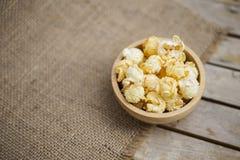 Rimmat popcorn i rund träbunke på hessianstygbakgrund Royaltyfri Fotografi