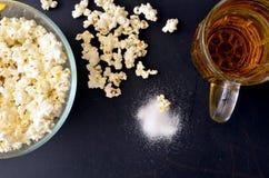 Rimmat popcorn och en råna av öl Royaltyfria Foton