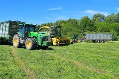 Rimorchi a due ruote di John Deere dei trattori con la raccoglitrice tagliata John Deere di foraggio e dell'erba Immagine Stock