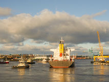 Rimorchiatore che assiste la nave da carico in serie per lasciare porto immagini stock libere da diritti