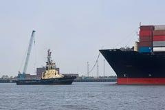 Rimorchiatore con la nave porta-container nel Regno Unito Fotografia Stock