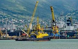 Rimorchiatore del porto nell'area dell'acqua del porto contro lo sfondo delle gru e delle navi del porto immagine stock libera da diritti