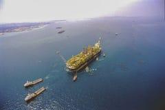 Rimorchiatori che portano l'impianto di perforazione del gas & del petrolio FPSO Immagini Stock