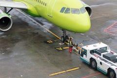 Rimorchio degli aerei dalla pista al parcheggio per mezzo di attrezzatura speciale Fotografia Stock